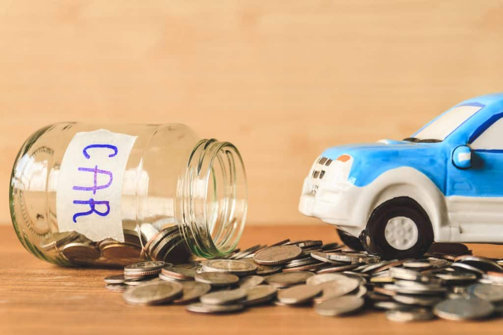 coins spilling out of glass jar, budgeting to buy a car