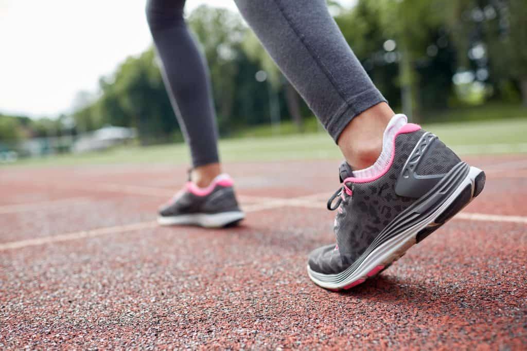 woman feet running on track